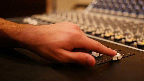 Male audio engineer using sound mixer in recording studio Live Action