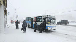 Group of people sit in public city bus during snowfall (snowstorm) Footage