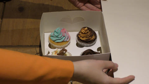 Box with cupcakes. The woman opens the box Live Action