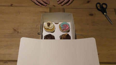 Box with cupcakes. The process of opening the box Live Action
