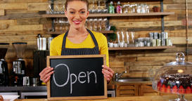 Smiling waitress showing slate with open sign, Live Action