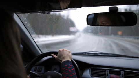 Lovely woman travelling by car on winter road Footage