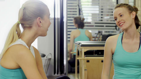 Beautiful woman interacting with trainer in fitness studio Live Action