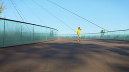 Child cruising on a pennyboard, down a bridge, slow motion Footage