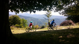 Father and sons on bicycles, mountain range Footage