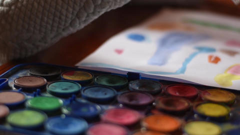 Young girl painting on a paper sheet with a watercolor brush. Dolly shot Footage