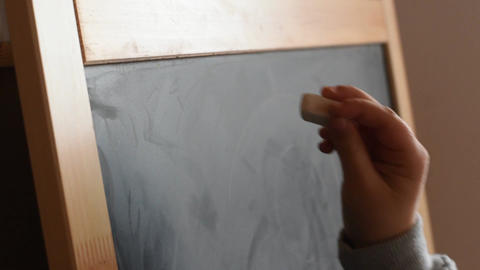 Young girl writing on a chalkboard with a piece of chalk. Close Up Live Action