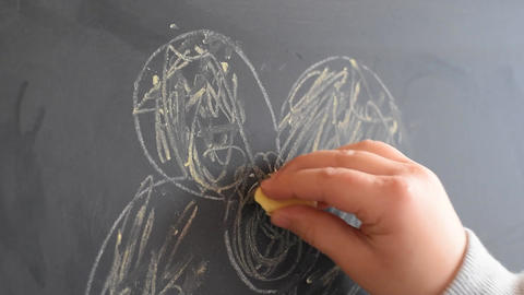 Young girl writing on a chalkboard with a piece of chalk.…, Live Action