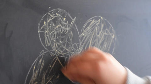 Young girl writing on a chalkboard with a piece of chalk.... Stock Video Footage
