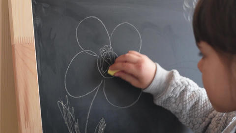 Young girl writing on a chalkboard with a piece of chalk. Close Up