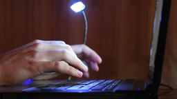 Hand typing on the computer keyboard, the keyboard is illuminated from above LED Footage