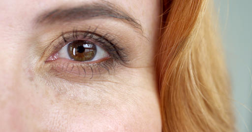 Extreme close-up of a brown eye of a woman with a foxy hair Footage