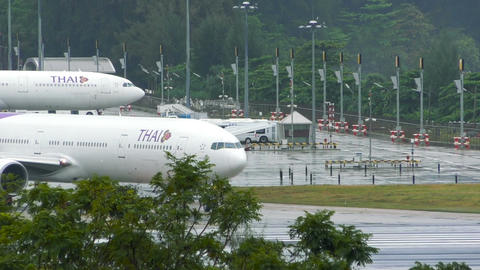 Boeing 777 taxis on wet runway after rain before taking off Footage