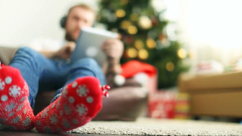 Man in bright Christmas socks using pad Footage
