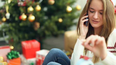 Pretty young girl in christmas cap talking on the phone Footage