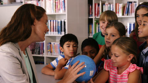 Teacher assisting school kids in reading globe in library Footage