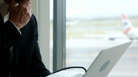 Businessman looking at laptop at airport Footage