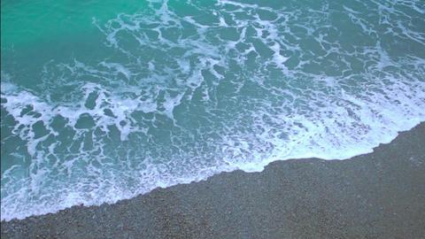 Green foamy ocean waves coming ashore, splashing on sand beach in slow motion Footage