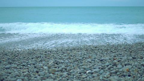 Turbulent foamy sea waves splashing ashore on pebble beach in slowmotion Footage