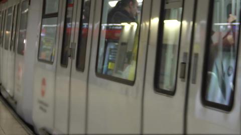 Subway train leaving platform, people walking in hall, public transportation Footage