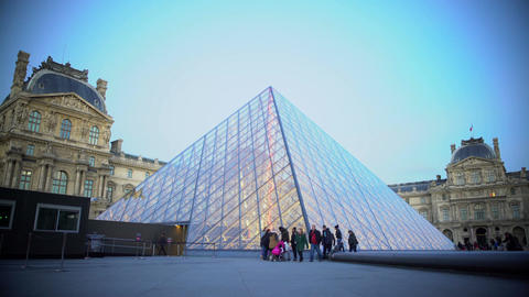 Groups of tourists walking by glass pyramid near Louvre Palace in Paris, France Footage