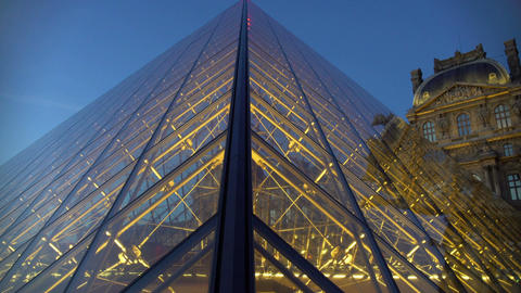 Art museum gallery seen through glass pyramid outside illuminated Louvre Palace Footage