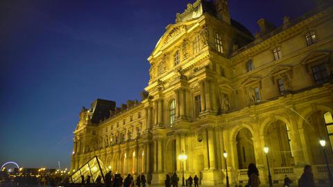 Crowd of people enjoying night view of Louvre Palace, sightseeing tour to Paris Footage