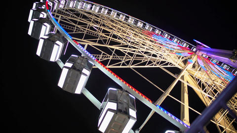 Huge Ferris wheel with illuminated passenger cars rotating fast, amusement ride Footage