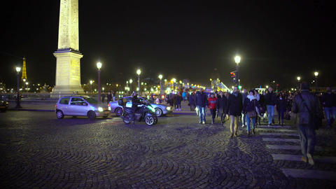Crowd of pedestrians crossing street, leaving Place de la Concorde, night Paris Footage