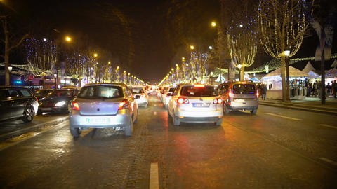 Festive atmosphere in night city, many cars on road, brightly illuminated street Footage