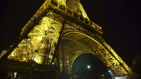 Grand iron construction of Eiffel Tower sparkling with lights in night Paris Footage