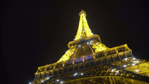 Eiffel Tower at night, huge iron construction sparkling brightly under dark sky Footage