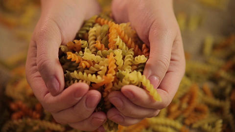 Colorful pasta in hands, Italian cuisine ingredient, healthy wholegrain product Footage
