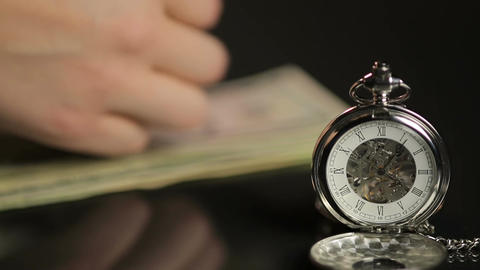 Male hands counting money behind expensive pocket watch, don't waste your time Footage