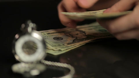 Person counting dollar bills, summing up investment results, watch showing time Footage