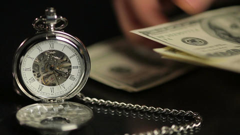 Hands counting money, person calculating savings, time flies on pocket watch Footage