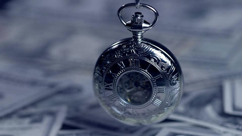 Vintage silver pocket watch hanging above pile of paper money, precious time ビデオ