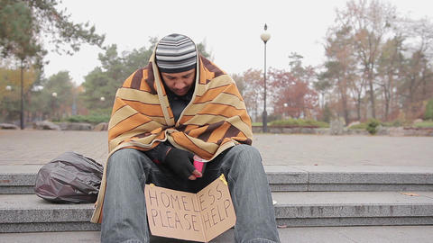 Poor man asking for charity in city park, miserable homeless person needs help Live Action