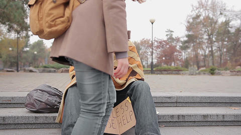 Kind young woman giving money to poor homeless man begging for help in street Live Action