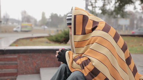 Unhappy male bum sitting alone in cold street, warming with coffee and blanket Live Action