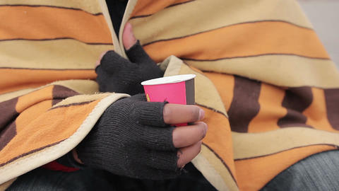 Poor man's hands holding paper cup for charity, goodhearted people giving money Live Action