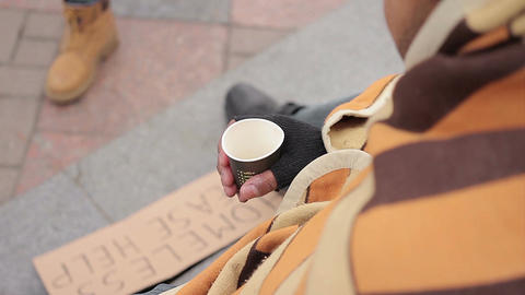 Poor person begging for charity in city street, sympathetic people giving money Live Action