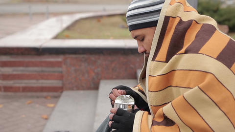 Hungry man eating canned food, homeless person sitting on ground, feeling cold Live Action