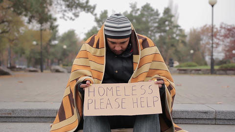 Poor homeless man sitting in cold street with help sign, begging for charity Footage