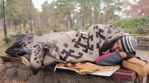 Poor homeless male lying on bench in cold city park covered with old blanket Live Action