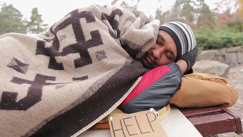 Sad homeless man suffering from cold, sleeping on bench covered with blanket Live Action