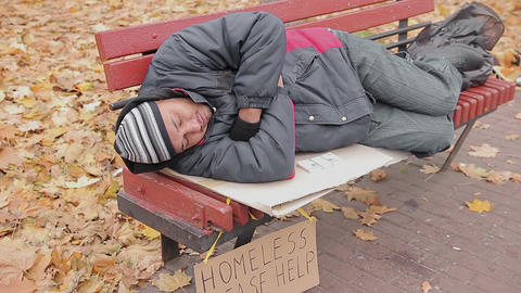 Anonymous benefactor giving generous charity donation to sleeping homeless man Footage