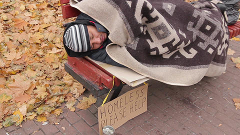 Miserable bum sleeping on bench with sign asking for help, homeless person Live Action