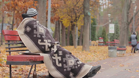 Homeless man sitting on bench with sad face, looking at people in autumn park Live Action