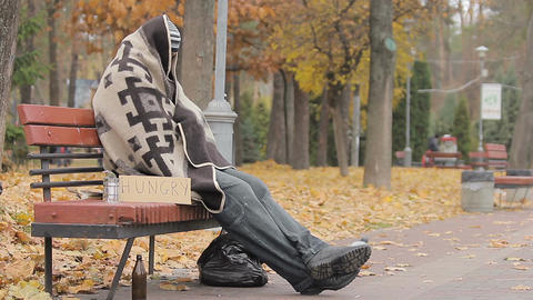 Desperate homeless person sitting on bench, hungry man begging for charity Footage